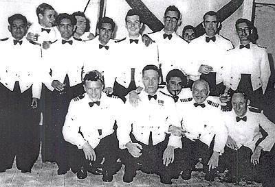 Aronda's officers during a BI anniversary party at Chittagong, September 15, 1956, including, from left front row, Chief Officer Henry Severs, Captain R S Freakes. ship's Surgeon (with pipe), Chief Engineer Officer W Oliver. Jack Hearne is second from right at the back with the Third Engineer on his left and Ist Radio Officer Dinjoe Murphy on his right